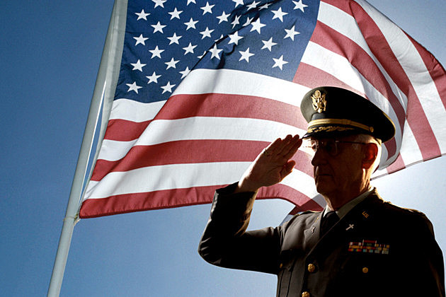 Silhouette of veteran US Army Colonel Chaplain wearing hat and saluting with an American flag flying behind him. - Thinkstock