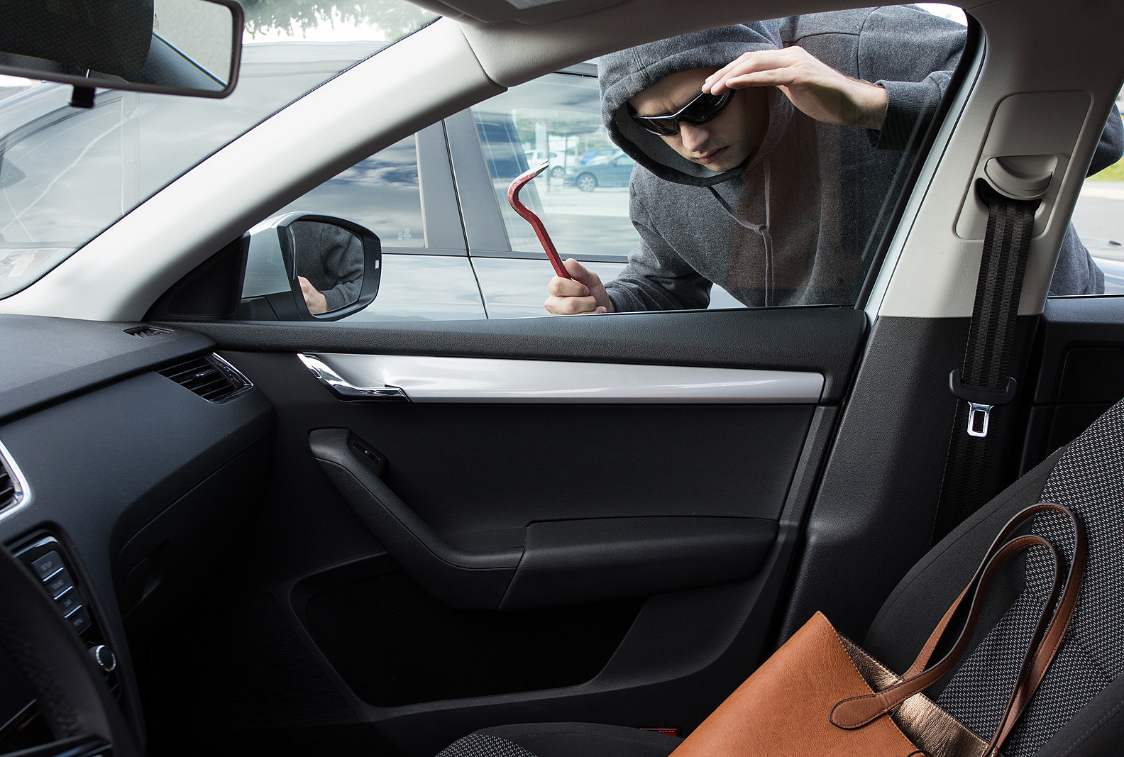 Thief wearing black hooded jacket and sunglasses is looking for unattended valuables left in a car. - Getty Images